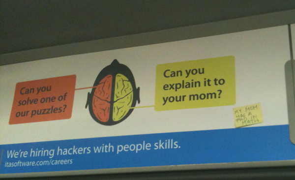 "Public transit ad depicting a brain: note pointing to one side says ""Can you solve one of our puzzles"" and the note pointing to the other side reads ""can you explain it to your mom?"". Text below reads ""We're hiring hackers with people skills"". Someone has added a post-it note to the advertisement which reads ""My mom has a PhD in math"""