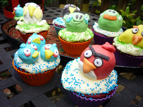 8 cupcakes in an assortment of coloured silicone cups with white icing and green or blue sprinkles. Each cupcake has a fondant angry bird or green pig atop it. There is one pig with bruises and the mustached pig. They are surrounded by the single big blue angry bird, a bundle of 3 little blue angry birds, the white bomber bird, the black bomb bird, the yellow torpedo bird and the red bird.