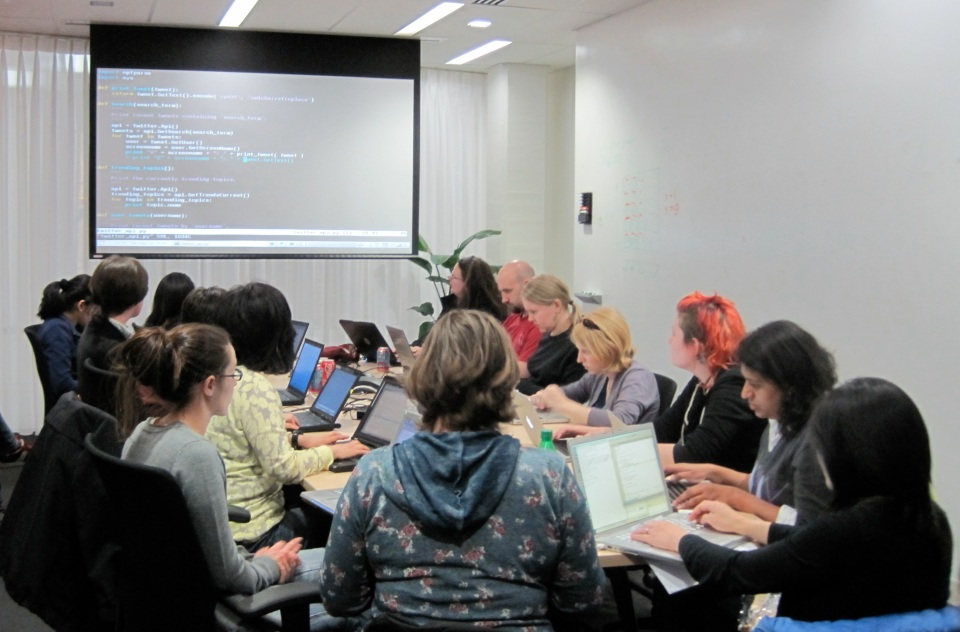 A breakout group at the Boston Python Workshop work at laptops around a table