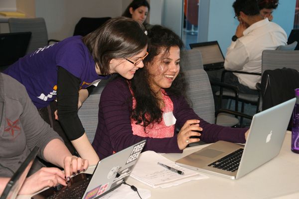 An instructor looks at a student's laptop at the Boston Python Workshop