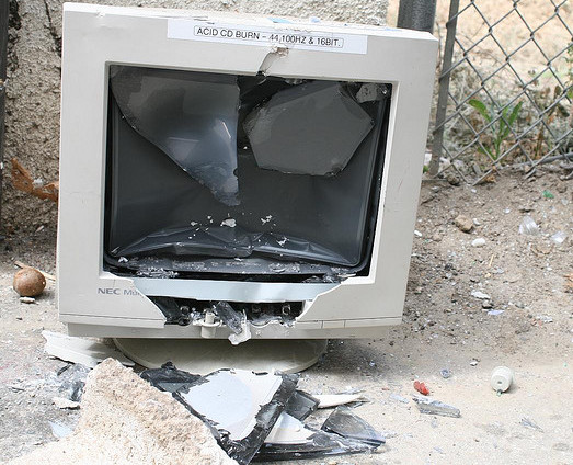 A computer monitor sitting on the ground, with the screen smashed