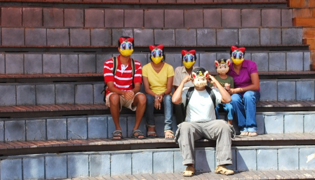 Masked by Harhsa K R (CC BY-SA): a group of people sitting on steps wearing duck and pig masks