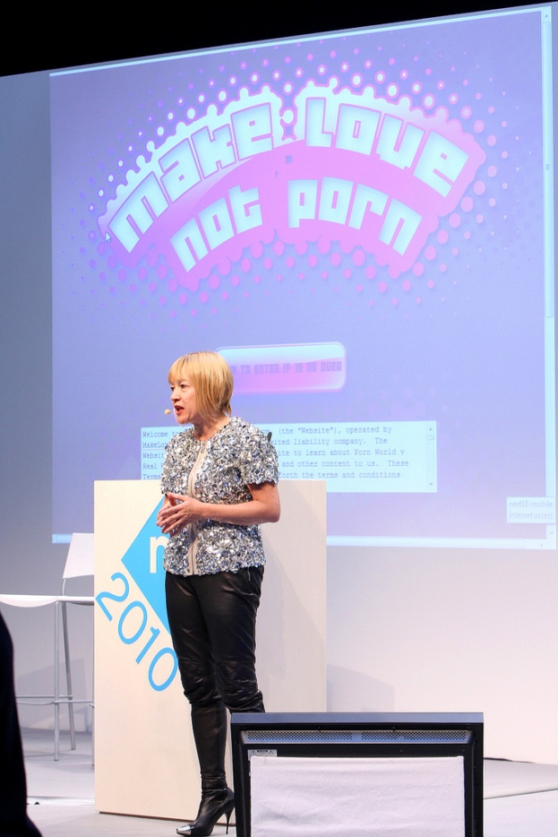 "Cindy Gallop stands in front of a presentation slide reading ""Make Love Not Porn"" by nextconf CC BY"