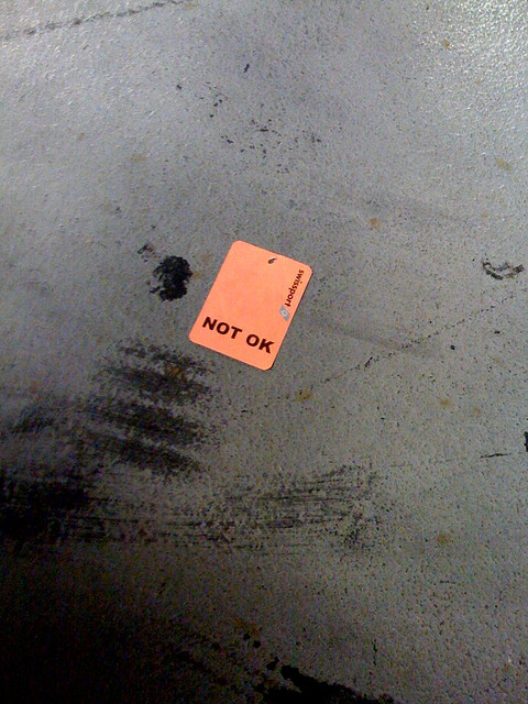 "Tag reading ""NOT OK"" lies on wet ground"