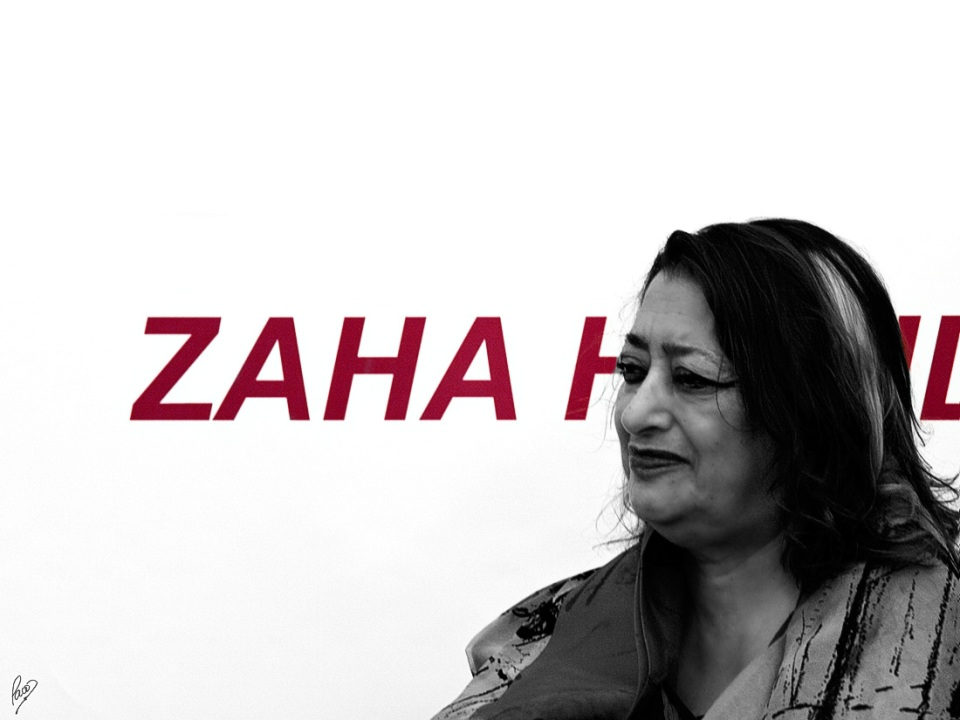 "Zaha Hadid stands in front of a white background with ""Zaha Hadid"" written on it in dark red by Paco CT CC BY-NC-SA"