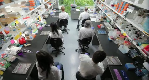 Screenshot from McGill Dances for Cancer Research Lipdub video: shows 6 researchers sitting in a biology lab