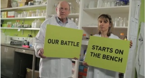 """Two cancer researchers holding signs """"Our battle"""" """"starts on the bench"""""""