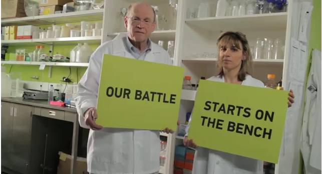 "Two cancer researchers holding signs ""Our battle"" ""starts on the bench"""