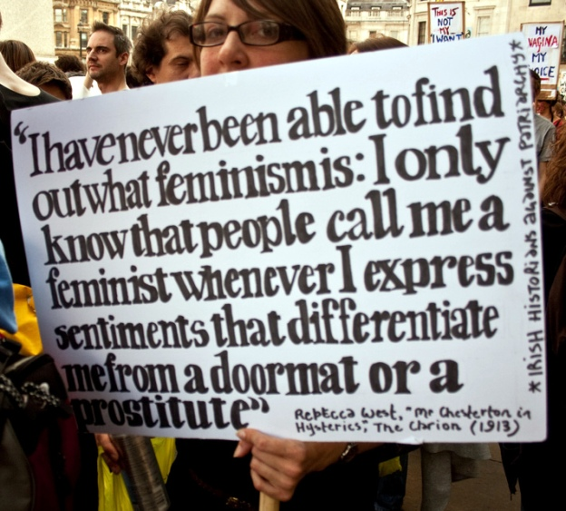 A woman holds a sign with Rebecca West's 'differentiate me from a doormat' quote