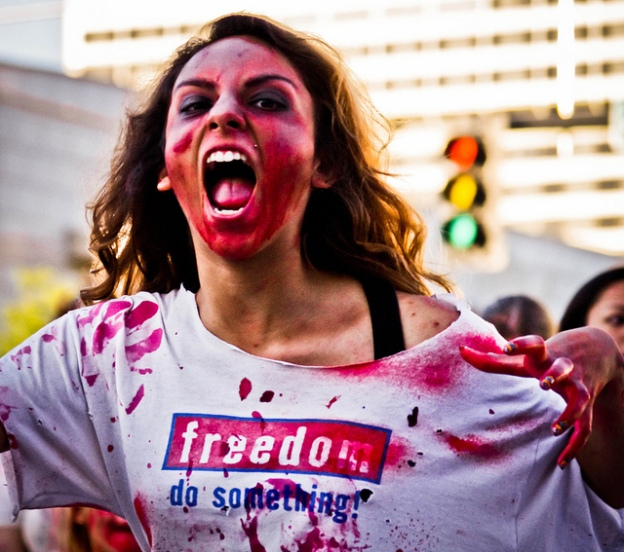 Angry woman covered in dark paint, wearing a shirt reading 'freedom'