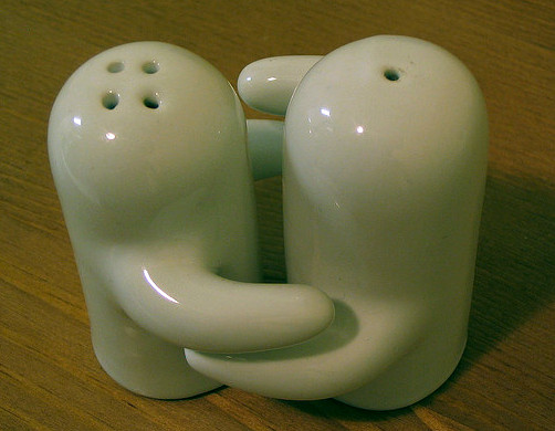 A salt and pepper shaker set with arms embracing each other