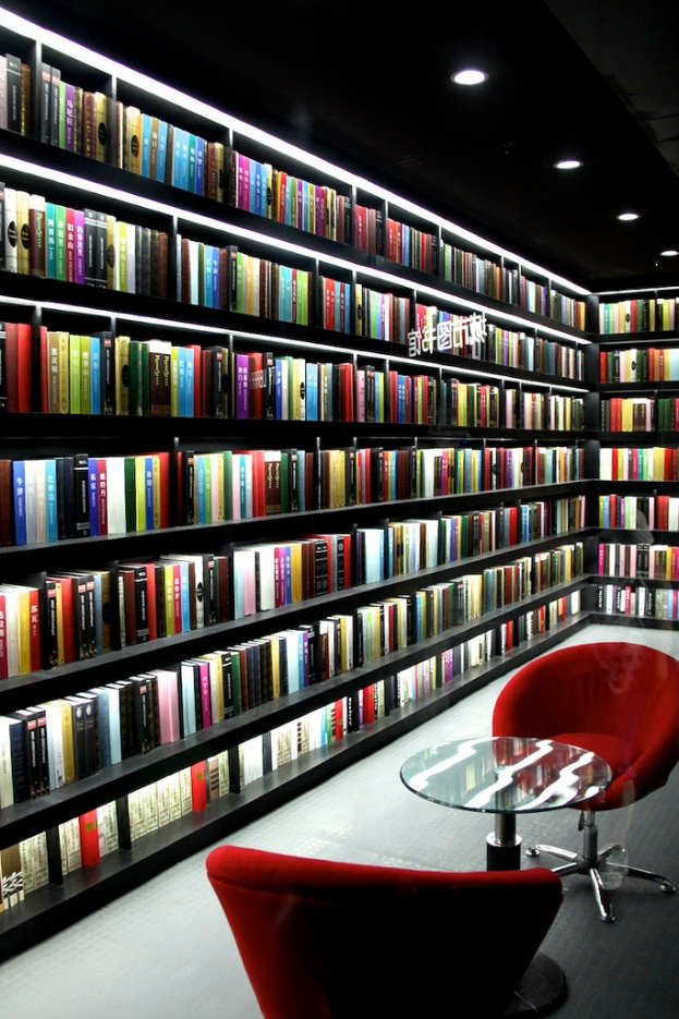 A photograph of luridly lit bookshelves surrounding a table and chairs