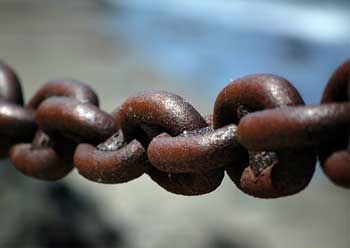 Close-up of large weathered chain links in sunlight.