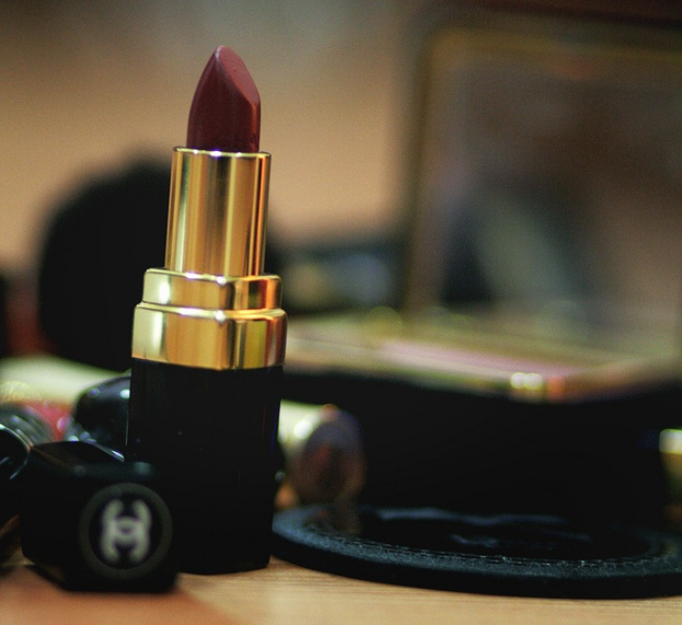 A closeup photograph of an open lipstick, with a blurry laptop in the background (by Aih)
