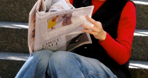 Neck-to-knee shot of woman in red top and jeans reading a newspaper, by Ed Yourdon, CC BY-SA