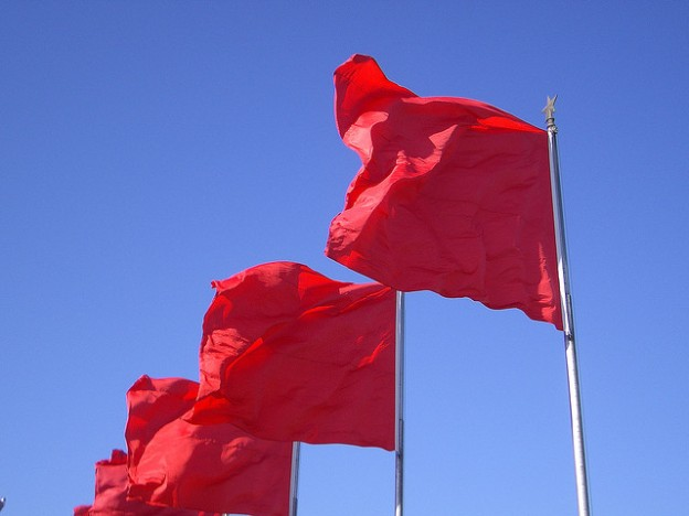 Three red flags in a stiff breeze