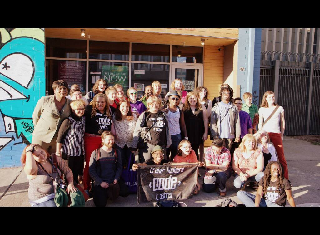 "A group photo of about 30 people, with the banner ""trans* hackers code it better"" in front"