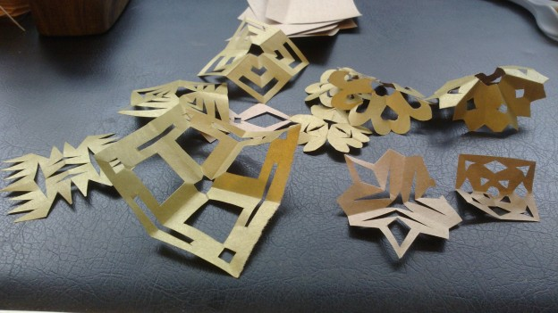 Several small snowflake-type papercraft pieces made from gold wrapping paper